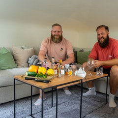 Zwei Männer sitzen auf Sofa vor einem mit Gin gedeckten Tisch