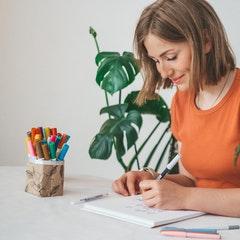 Frau schreibt auf Blatt Papier