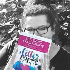 Foto von Lieber Rosa mit Buch in der Hand