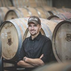 Foto von Mann vor Weinfässern