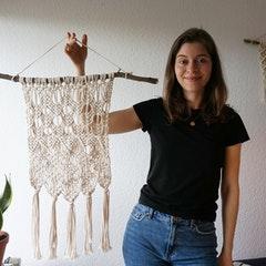 Foto von Frau mit Makramee-Kunstwerk in der Hand