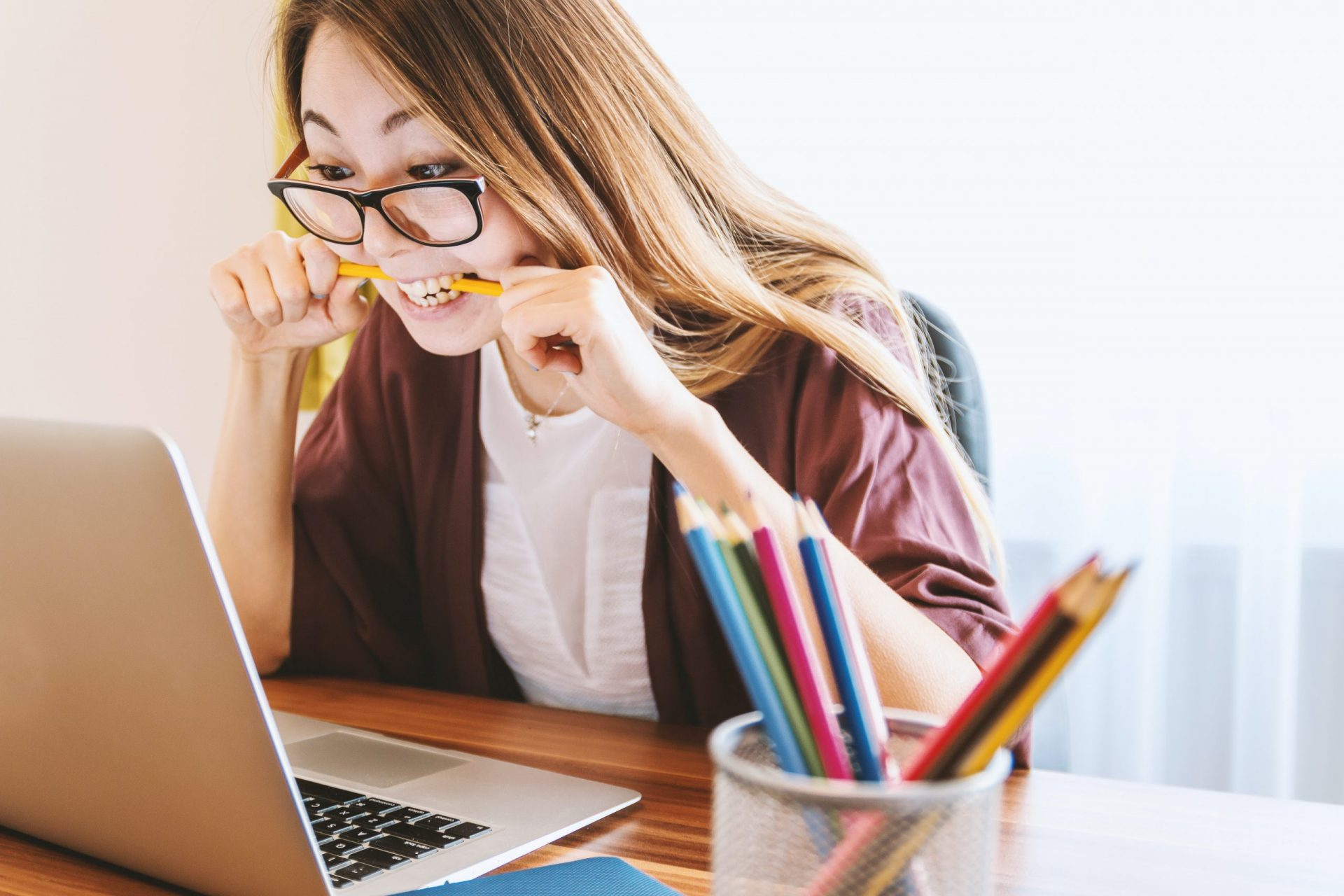 Frau kaut Bleistift vor Laptop