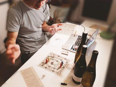 Mann spielt Brettspiel und trinkt Wein