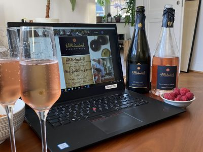 Aufgeklappter Laptop und Wein auf Tisch