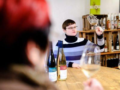 Frau begutachtet Wein in Glas