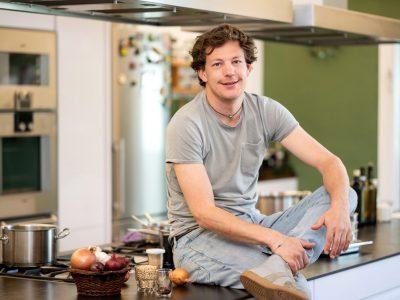 Mann sitzt auf Küchenarbeitsplatte
