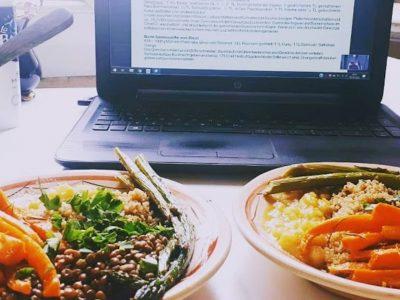 Zwei Teller mit Essen vor Laptop