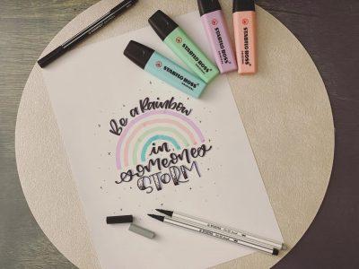 Regenbogen und schöne Schrift auf Blatt Papier