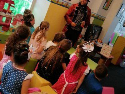 Zauberer führt Zaubertrick vor Kindern vor