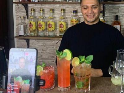 Mann präsentiert Cocktails vor Smartphonekamera