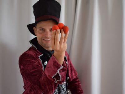 Zauberer zaubert mit Bällen